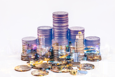 Double exposure of coin stacks isolated modern city night background. Saving, Investment money concept. Coin stack growing business. Banco de Imagens