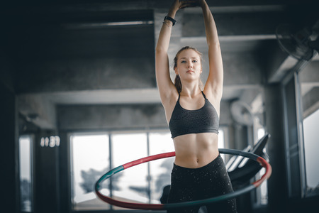 Beautiful caucasian young woman doing hoop in step waist hooping forward stance. Young woman doing hoop during an exercise class in a gym. Healthy sports lifestyle, Fitness, Healthy concept.