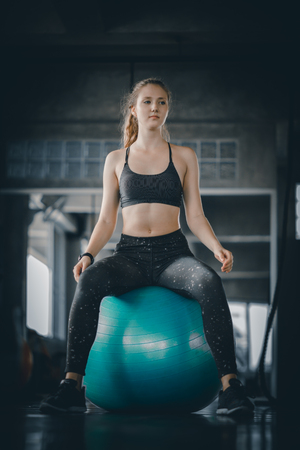 Young attractive woman fitness doing exercises workout on ball in gym. Woman stretching the muscles and relaxing after exercise at fitness gym club.