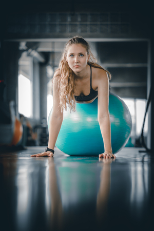 Young attractive woman fitness doing hard difficult plank on ball in gym workout. Woman stretching the muscles and relaxing after exercise at fitness gym club. Banco de Imagens