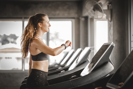 Fit young woman caucasian running on machine treadmill workout in gym. Glad smiling girl is enjoy with her training process. Concept of fitness, healthy life, Sport, Lifestyle. Banco de Imagens