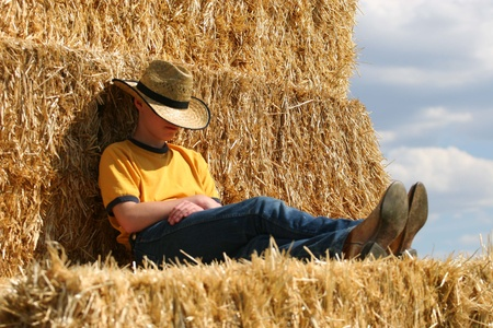 Cowboy asleep with hat pulled down on straw stack photo