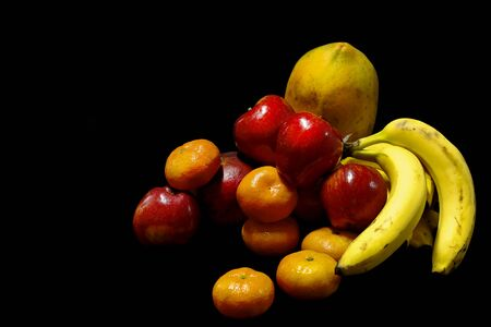 Arrangement of fruit still life with black background and tropical fruits such as papaya, apple, tangerine and bananas