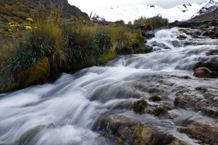 View on a cloudy day of the snowy Huaytapallana next to a small river in the central mountain range of the Peruvian Andes Reklamní fotografie