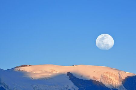 Moon on a summit of the snowy Huaytapallana, achieved using a double exposure from the camera.