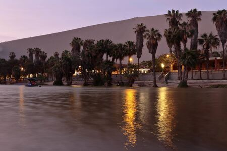 Beautiful view at dusk from the shore of the Huacahina oasis, observing the palm trees, the water and the desert in the blue hour. Ica-Peru Standard-Bild