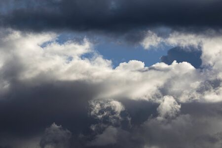 Detail of towering dramatic clouds in the Andean skies, stormy cloud formations laden with water about to precipitate, contrasted by the afternoon lights.