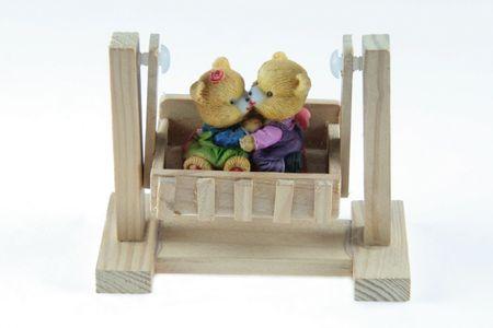 love bears figurine in a wooden swing