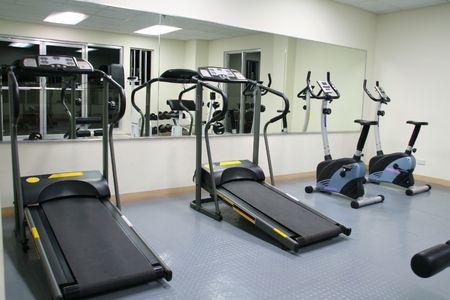 exercise gym with large mirrors, treadmills and stationary bikes
