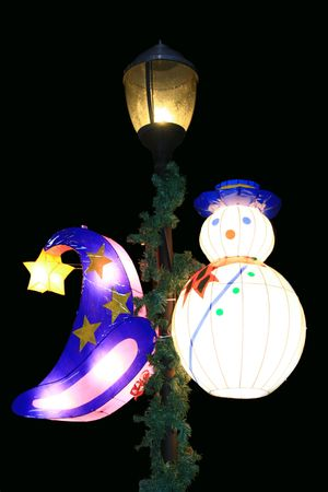 wizard hat and snowman lanterns hanging at a lamp post
