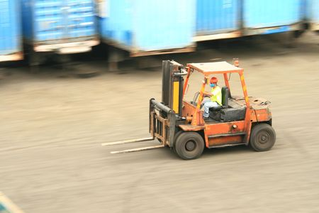 orange forklift in motion at a  ship port Stock Photo