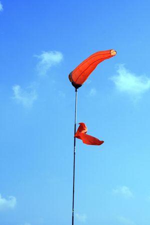 orange wind sock against a clear blue sky