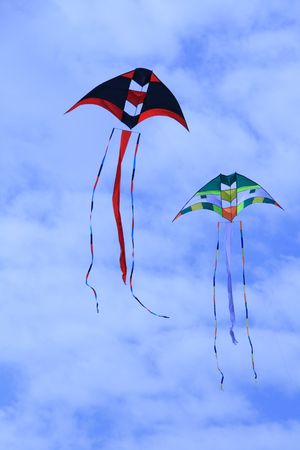 two colorful kites flying against a blue sky