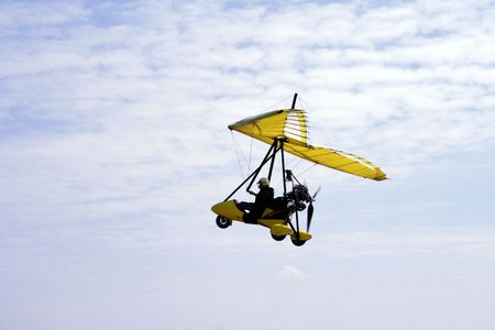 ultralight aircraft in flight against the blue sky Stock Photo