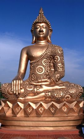 statue of a golden buddha against a blue sky Stock Photo