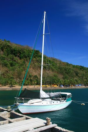 sail boat docked at a pier of a resort Stock Photo