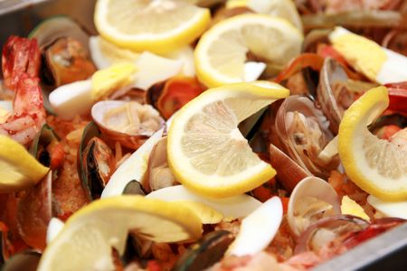 close-up of seafood paella with lots of lemon toppings Stock Photo