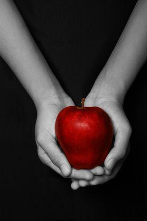 manos la celebración de una manzana roja en fondo negro Foto de archivo