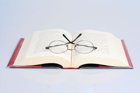 open book with a pair of eye glasses on top photo