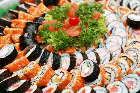 a variety of japanese maki served in a tray