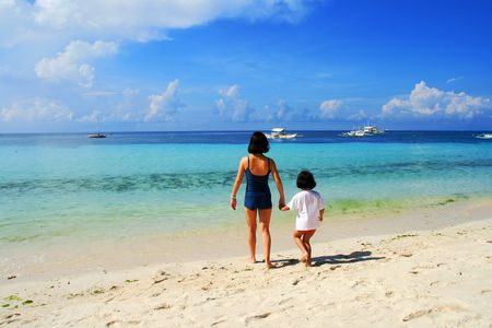 mother and daughter walking side by side on a beach Stock Photo