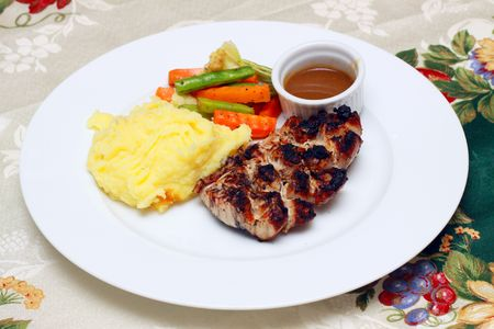 grilled fish stake served with mashed potato and vegetables