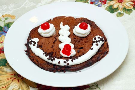 chocolate flavored pancake with white icing and cherries