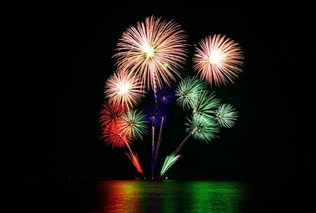 very colorful fireworks launched at a floating barge