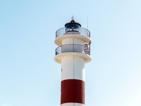 Lighthouse with red stripe and balcony