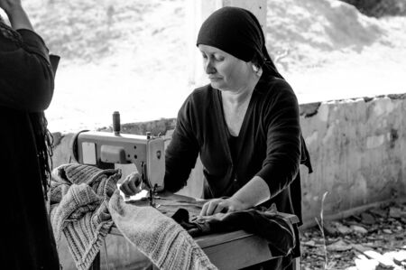Seamstress with head scarf Stock Photo