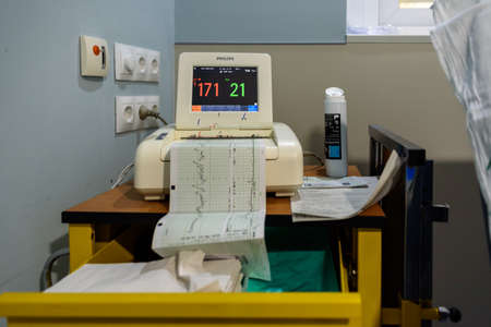 EKG machine in hospital ward with paper charts of woman in labor