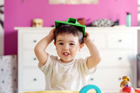 Cute little boy playing in room at home with various toys