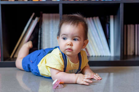 little baby lying on the floor face down with yellow t-shirt in front of books Foto de archivo