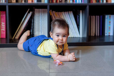 little baby lying on the floor face down with yellow t-shirt in front of books