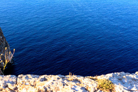 seascape with cliff by the calm blue sea and clear sky