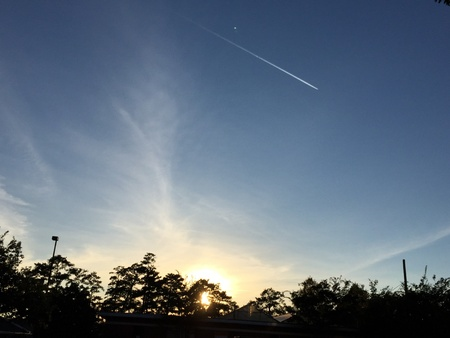 A plane and its contrail streak past a sunset in Auburn, Alabama