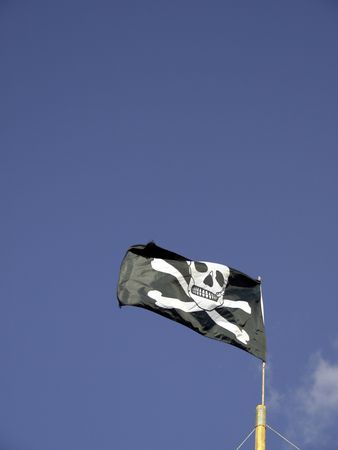 pillage: A jolly roger skull and crossbones flag flutters against a blue sky