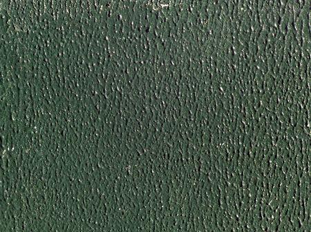 stippled: Sunlight highlights green stippled paint on board