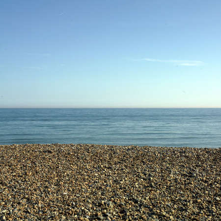 seafreight: Blue sea and sky with a pebbly shingle beach Stock Photo