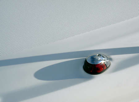 nonslip: Red coloured port side navigation lamp on a motor cruiser and white non-slip deck Stock Photo
