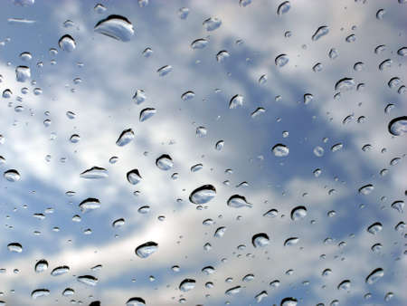 blustery: Rain drops on window with cloudy blue sky in the background