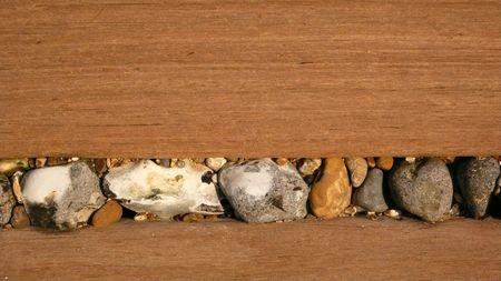 groyne: Stones lodged in a wooden sea defence groyne