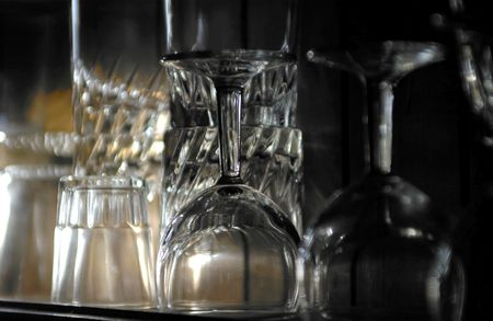 sidelit: Assorted sidelit drinking glasses stacked on a shelf