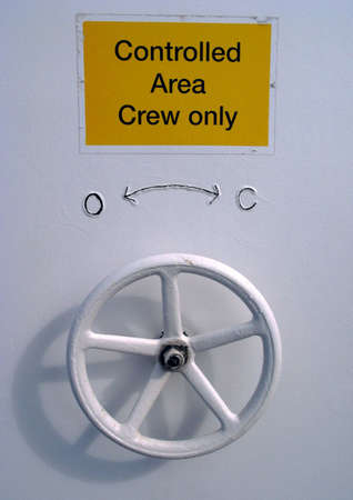 watertight: Control sign and opening closing wheel on a ships watertight door. Stock Photo