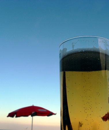 amber coloured: Glass of amber coloured beer against a blue sky with a red parasol. Stock Photo