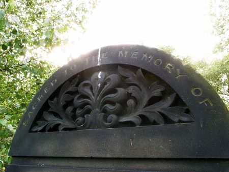 cemetry: A dark gravestone sacred to the memory of the dead.
