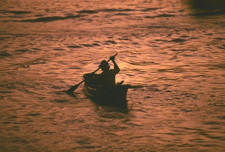 paddler: A lone paddler on a copper coloured Chao Prya river at sunset Stock Photo