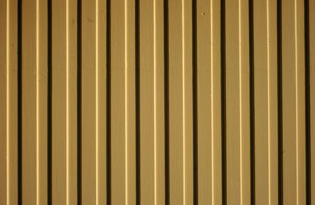 fence panel: A sunlit clapboard wood painted fence panel.