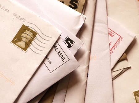 A pile of business mail in unopened envelopes awaits attention. Stock Photo