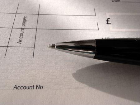 biro: Black and chrome biro pen and blank cheque.